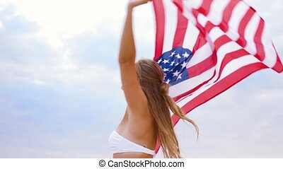 happy young woman with american flag on beach - patriotism,...