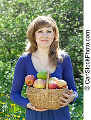 woman with apple harvest in orchard