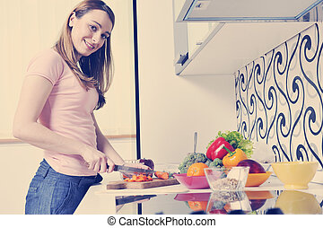 happy young  woman with apple in kitchen