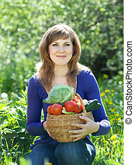 woman with basket of harvested vegetables in garden