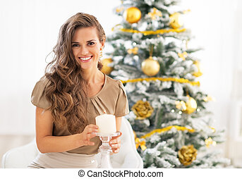 Happy young woman with candle near christmas tree