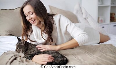 happy young woman with cat eating in bed at home