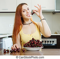 woman with cherries in home kitchen