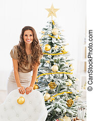 Happy young woman with christmas ball near christmas tree