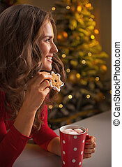 Happy young woman with christmas cookie and cup of hot chocolate