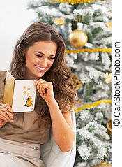 Happy young woman with christmas letter near christmas tree