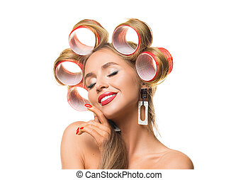 Happy young woman with closed eyes and hair curlers on her head isolated on white.