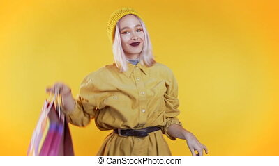 Happy young woman with colorful hair and paper bags after shopping isolated on yellow studio background. Seasonal sale, purchases, spending money on gifts concept