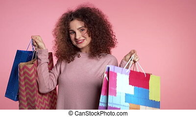 Happy young woman with colorful paper bags after shopping isolated on pink studio background. Seasonal sale, purchases, spending money on gifts concept