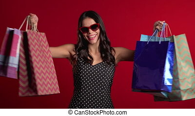 Happy young woman with colorful paper bags after shopping isolated on red studio background. Seasonal sale, purchases, spending money on gifts concept
