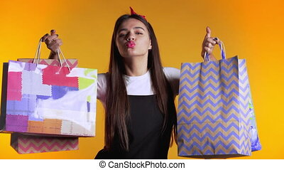 Happy young woman with colorful paper bags after shopping isolated on yellow studio background. Seasonal sale, purchases, spending money on gifts concept