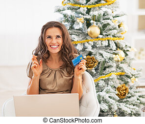 Happy young woman with credit card and laptop near christmas tree crossed fingers