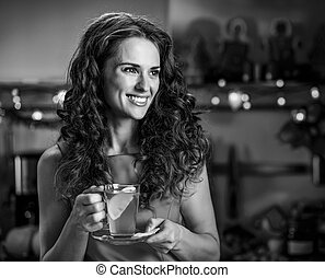 Happy young woman with cup of ginger tea looking on copy space