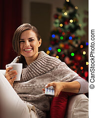 Happy young woman with cup of hot beverage near christmas ...