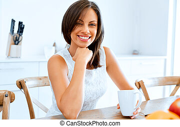 Happy young woman with cup of tea or coffee at home
