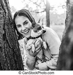 Happy young woman with dog outdoors in autumn park looking out from from tree