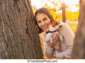 Happy young woman with dog outdoors in autumn park looking out f