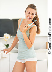 Happy young woman with electric toothbrush in bathroom