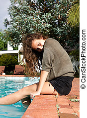 Happy young woman with feet in pool