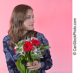 happy young woman with flowers on pink background