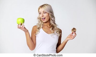 happy young woman with green apple and cookie - healthy...
