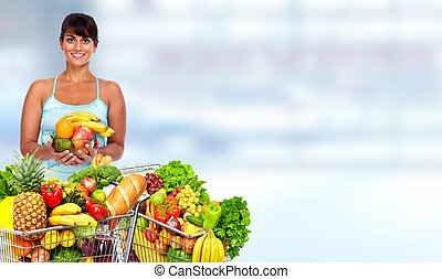 Happy young woman with grocery shopping cart.