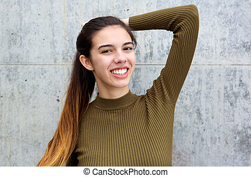 Happy young woman with hand in hair