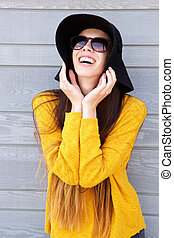 Happy young woman with hands by face in sunglasses