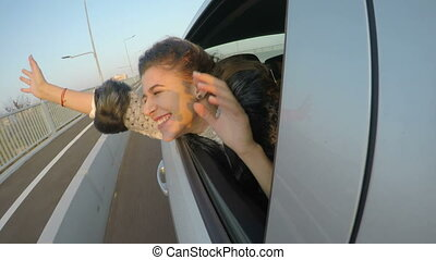 Happy young woman with hands out the car window enjoying the ride