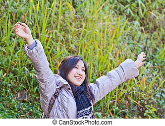Happy young woman with hands up