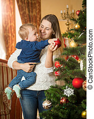 Happy young woman with her baby son decorating Christmas tree