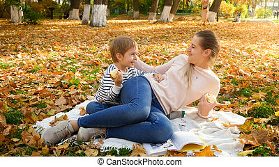 Happy young woman with her little son lying on blanket at autumn park and smiling at each other