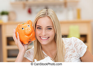 Happy young woman with her piggy bank