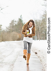 Happy young woman with hot beverage walking in winter park