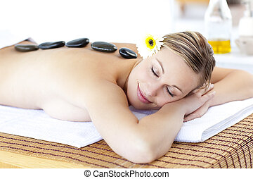 Happy young woman with hot stone on her back and closed eyes