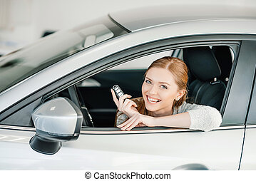 Happy young woman with key sitting in new car
