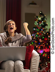 Happy young woman with laptop near christmas tree rejoicing