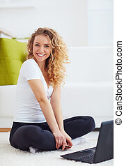 happy young woman with laptop, sitting on carpet at home