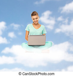 happy young woman with laptop sitting on cloud
