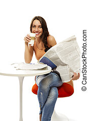happy young woman with latte macchiato coffee and a newspaper on white background