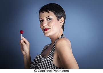 happy young woman with lollipop in her mouth on blue background
