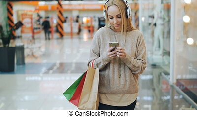 Happy young woman with long blond hair is listening to music through headphones and using smartphone while walking in shopping mall with paper bags.