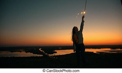 Happy young woman with long hair flying in the wind raising...