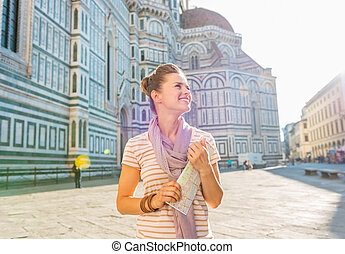 Happy young woman with map in front of cattedrale di santa ...