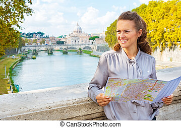 Happy young woman with map on bridge ponte umberto I with view o