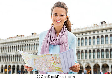 Happy young woman with map on piazza san marco in venice, italy