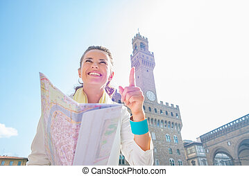 Happy young woman with map pointing in front of palazzo vecchio