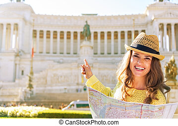 Happy young woman with map pointing on piazza venezia in rome, i