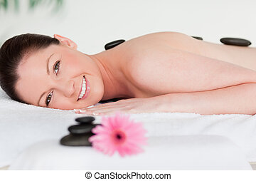 Happy young woman with massage stones