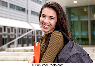 Happy young woman with notebook and backpack